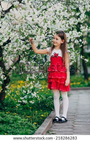 caucasian small and pretty girl stay under apple tree flowers