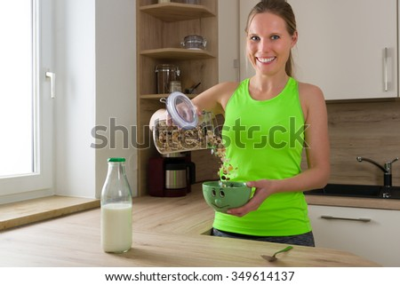 Caucasian woman in gym suit mixing cereals (muesli) with milk for breakfast in the kitchen