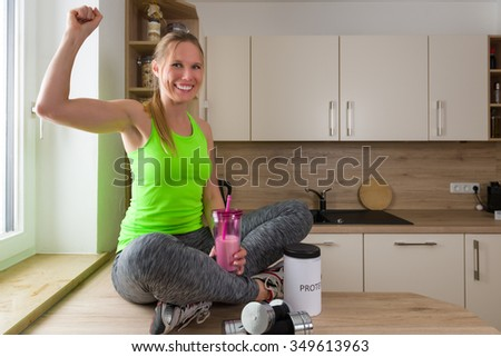 Caucasian woman in gym suit with protein drink in victory pose.