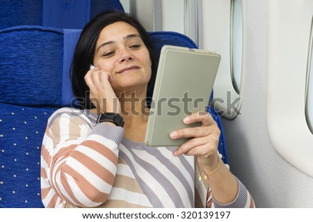 caucasian woman passenger in airplane using mobile and  tablet smart devices