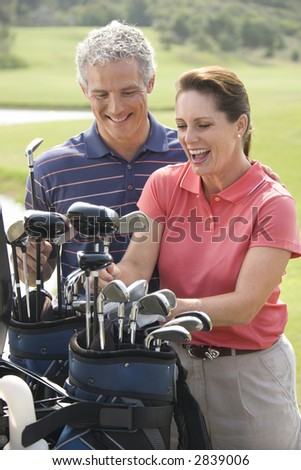 Caucasion mid-adult man and woman smiling and picking out golf club.