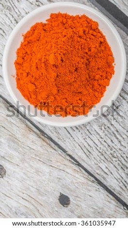 Cayenne red pepper powder in white bowl over wooden background
