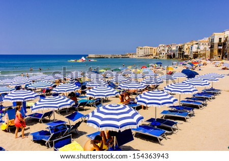 CEFAL��, SICILY, ITALY â�� JULY 17: Parasols on the beach on July 17, 2013 in Cefal�¹, Sicily. Cefal�¹ is one of the most popular destinations for a Sicilian vacation.