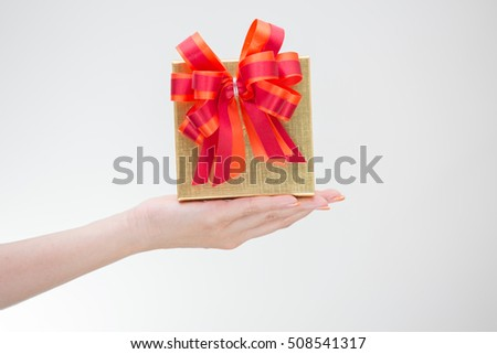 Celebrate 2017. Woman hand holding golden gift box for Christmas and Happy new year 2017 background