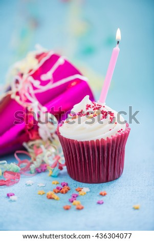 celebrating birthday with cupcake and candle on blue background