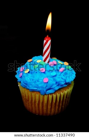Celebration cupcake with lit candle on black background.