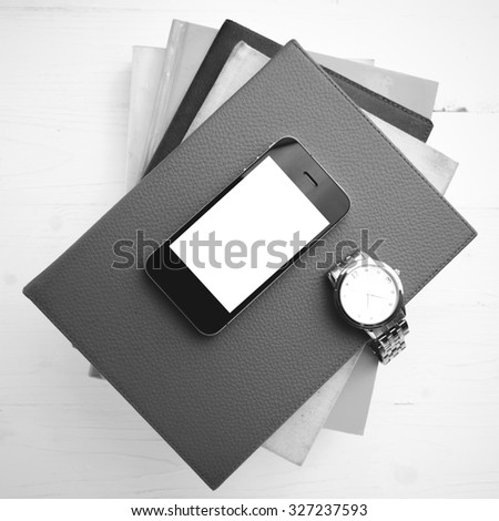 cellphone with stack of book and watch over white table black and white tone color style