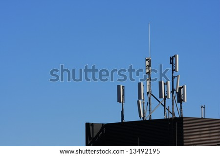 Cellular telephone system aerials on the skyline in a modern city.