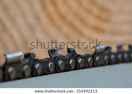 Chain of chainsaw with wood in background