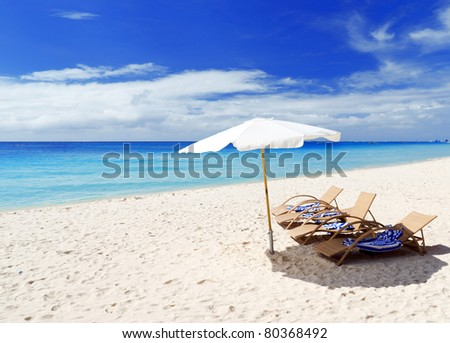Chairs on white sand beach.
