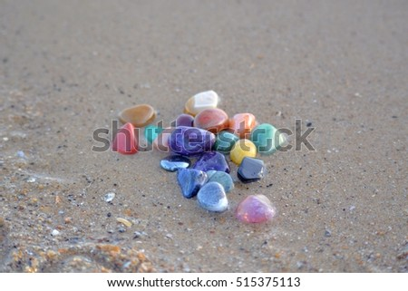 chakra stones in wet sand for cleansing in the sea