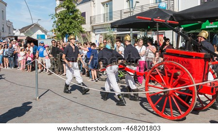 "Challans, France - August 11, 2016 : event ""Once Challans"" organized by the city and plunges visitors into the city from the early 20th century - antique firefighters to intervene with a water pump"