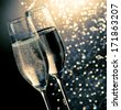 champagne flutes with golden bubbles on dark blue light bokeh background with space for text - stock photo
