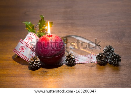 champagne glass, christmas ribbon, candle, cones and holly branch on wooden