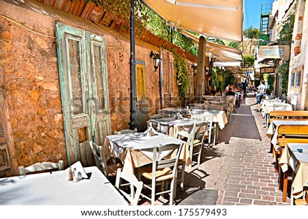 CHANIA, GREECE - OCTOBER 14, 2013: The cafe is located in the narrow lane, walls of houses are decorated with doors with old peeling paint, on October 14,2013 in Chania.