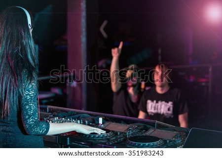 Charismatic disc jockey at the turntable. DJ plays on the best, famous CD players at nightclub during party and his crowd.