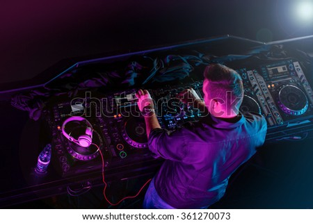 Charismatic disc jockey at the turntable. DJ plays on the best, famous CD players at nightclub during party. Selective focus.