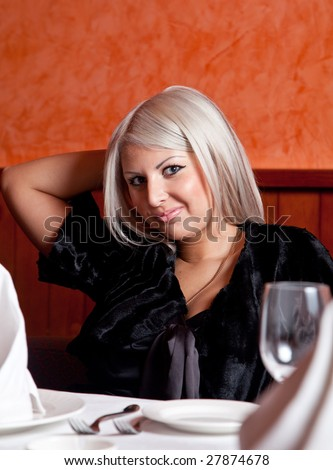 Charming blond girl sitting at a table in a restaurant