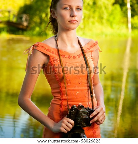 Charming girl with camera stands on bank of beautiful lake.