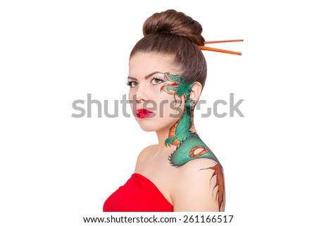 Charming girl with the dragon tattoo drawn on his face isolated on white background
