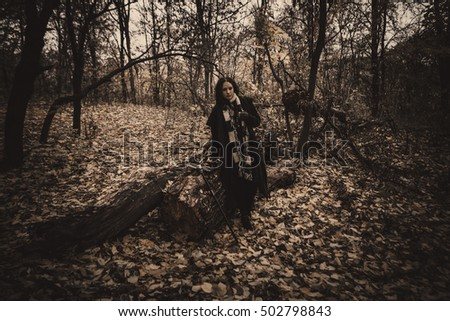 Charming lady with dreadlocks wearing black mantle standing by the old tree in the autumn forest. Fantasy and Halloween image.