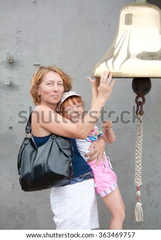 Charming woman and happy child touching the ship's bell