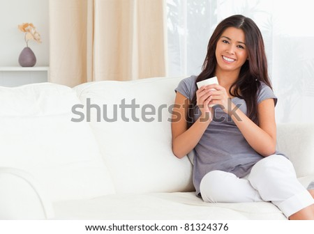 charming woman with cup looking into camera in living room