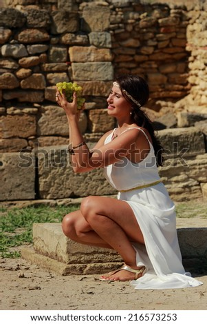 Charming young girl with beautiful hair in the Greek style eats white grapes on a background of the excavations of the ancient Greek city of Nymphaeum, Kerch, Russia