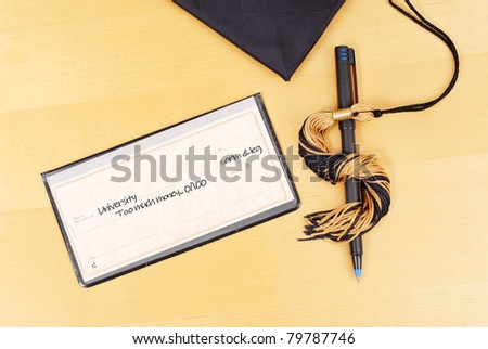 Check with Pen and Tassel in Shape of Dollar Sign