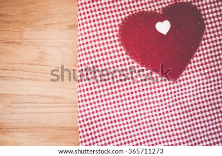 checkered cotton fabric and heart felt decoration on a wood background