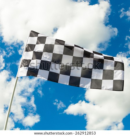 Checkered flag waving in the wind with clouds on background - outdoors shoot