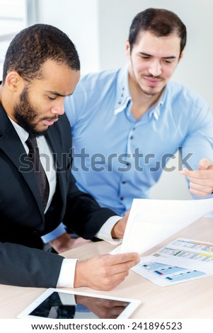 Checking the business contract. Two successful businessman sitting at the negotiating table in the office and working at his laptop. Business people dressed in formal wear