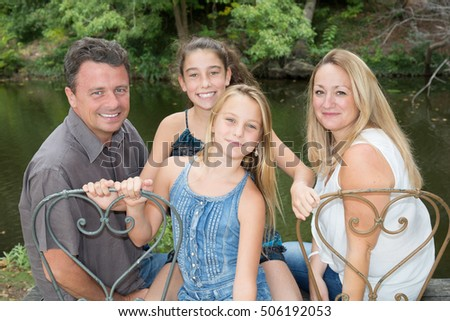 Cheerful and loving family on the bench at park