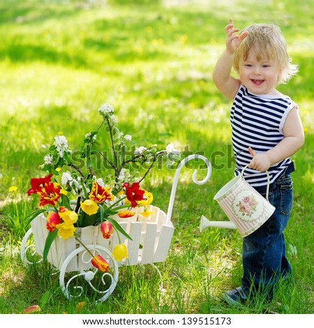 Cheerful baby boy outdoors with watering can and spring flowers in the wooden decorative wheelbarrow