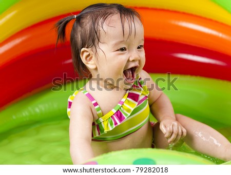 Cheerful baby girl playing in wading pool