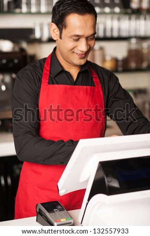 Cheerful barista staff cross-checking the order before billing the same.