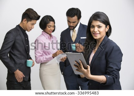 Cheerful businesswoman holding tablet  with her colleagues on white background.