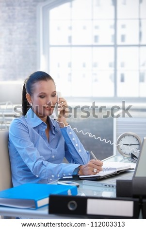 Cheerful businesswoman on landline call, taking notes, smiling.