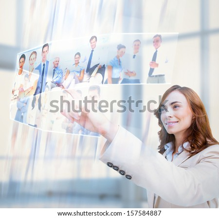 Cheerful businesswoman scrolling pictures on digital screen