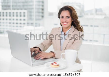 Cheerful businesswoman using laptop at her desk and having coffee in her office