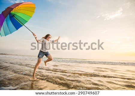Cheerful caucasian young woman with rainbow umbrella having fun on the Jimbaran beach on Bali before sunset with beautiful ocean and blue sky on background. Travel, holidays, vacation, healthy