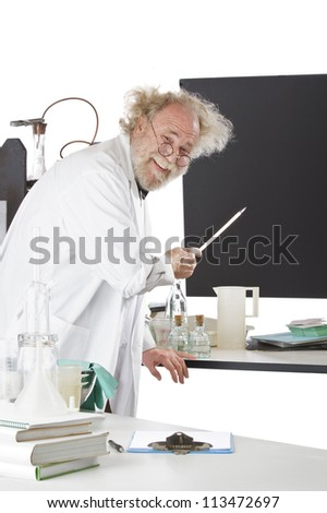Cheerful eccentric senior scientist in his lab points to blackboard and explains his ideas. High key, vertical, copy space.
