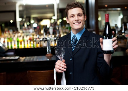 Cheerful executive posing with a bottle of wine. Bar in the background
