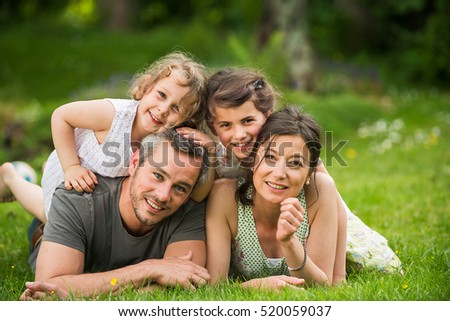 Cheerful family in a park, Dad, mom and their two lovely daughter are lying on the grass while they are looking at camera