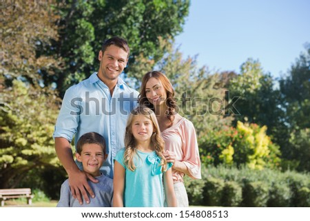 Cheerful family standing in the countryside smiling at camera