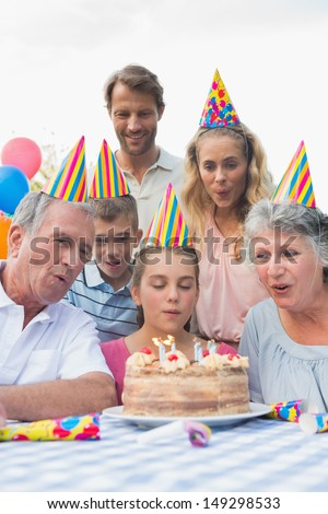 Cheerful family watching girl blowing out candles at birthday party outside at picnic table