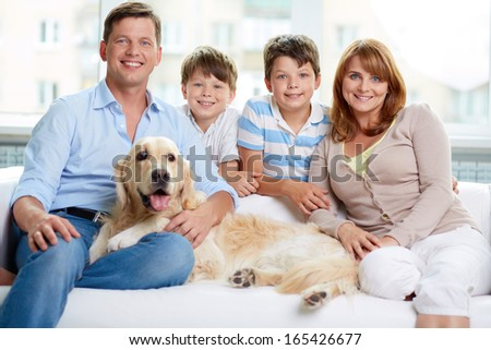 Cheerful family with their pet sitting on sofa at home