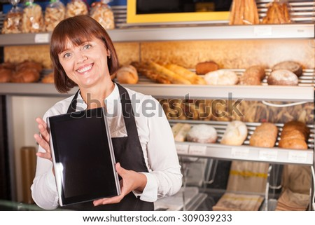Cheerful female baker is showing a tablet with recipe to the camera. She is standing near shelf of baked products and smiling. Copy space in right side
