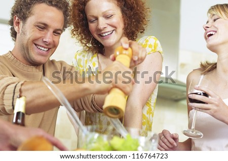 Cheerful friends having a good time while they preparing a meal together