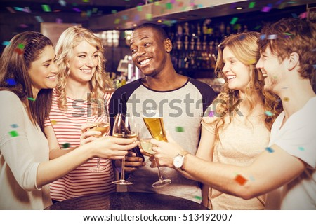 Cheerful friends toasting with beer and wine against flying colours